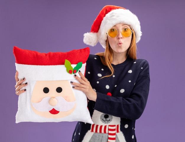 紫色の背景で隔離のクリスマス枕を保持しているメガネとクリスマスセーターと帽子を身に着けている心配の若い美しい少女