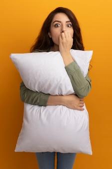 La giovane bella ragazza interessata che porta la maglietta verde oliva ha abbracciato il cuscino morde le unghie isolate sulla parete gialla