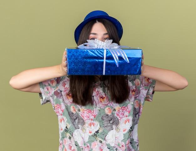La giovane bella ragazza interessata che indossa il cappello da festa ha coperto il viso con una confezione regalo isolata su una parete verde oliva