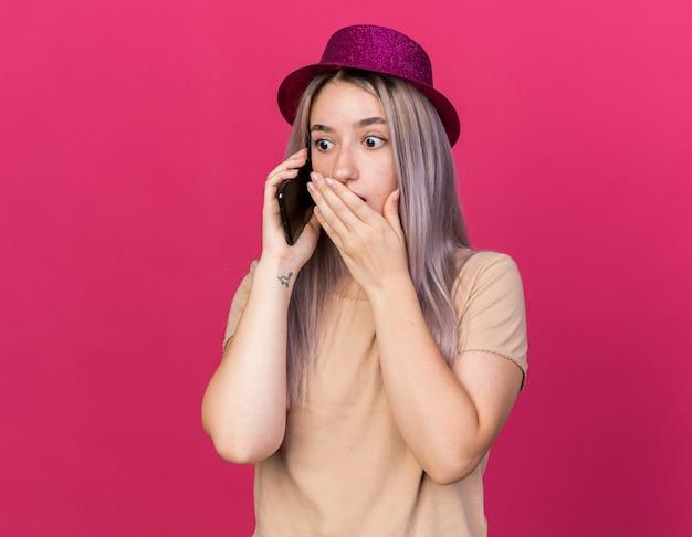 パーティーハットをかぶって心配している若い美しい女の子が電話で話します