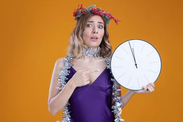 Preoccupato per la giovane bella ragazza che indossa un abito viola e una corona con una ghirlanda sul collo e indica l'orologio da parete isolato su sfondo marrone
