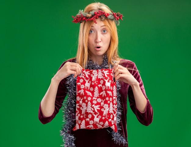 緑の背景で隔離のクリスマスバッグを保持している首に花輪と花輪と赤いドレスを着て心配している若い美しい少女