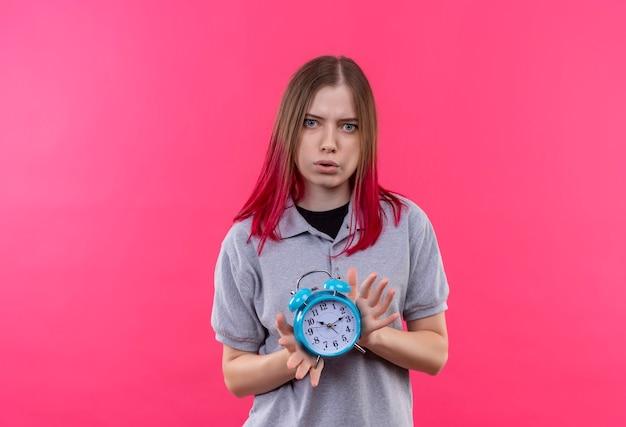 孤立したピンクの壁に目覚まし時計を保持している灰色のtシャツを着て心配している若い美しい女性