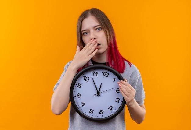 孤立した黄色の壁に手で壁時計で覆われた口を保持している灰色のtシャツを着て心配している若い美しい女性