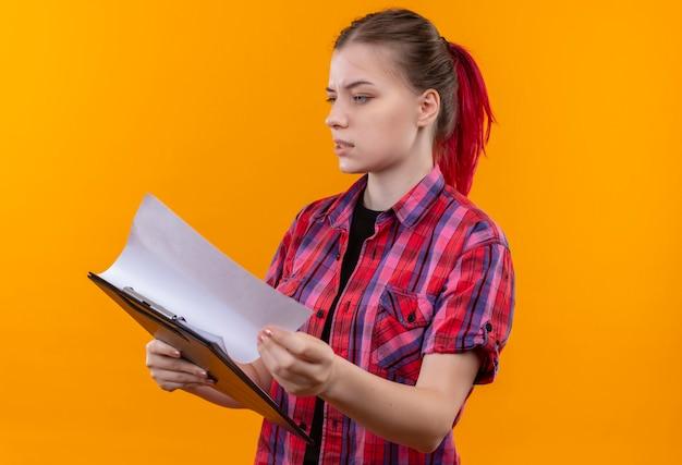 孤立した黄色の壁にクリップボードをめくって赤いシャツを着ている心配している若い美しい女性