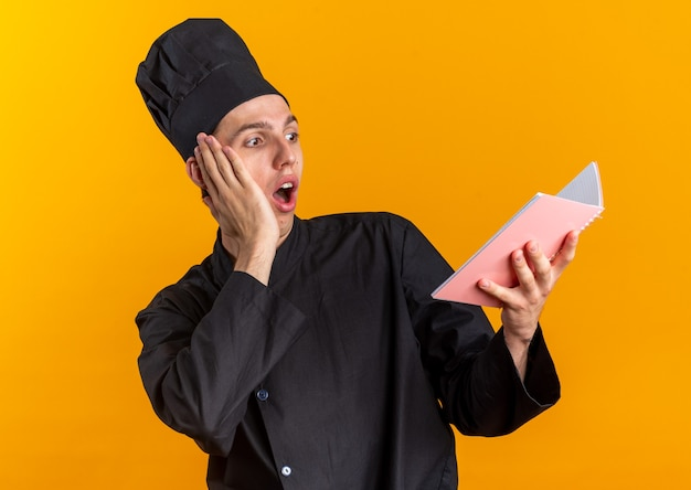 Concerned young blonde male cook in chef uniform and cap keeping hand on face reading note pad isolated on orange wall
