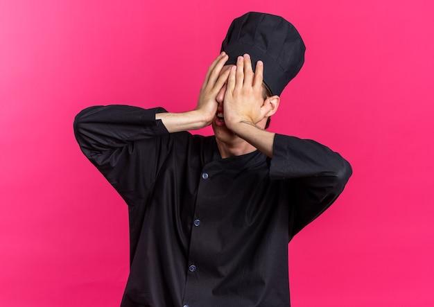 Озабоченный молодой блондин мужчина-повар в униформе шеф-повара и кепке держит руки на лице, закрывая глаза
