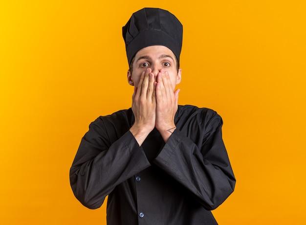 주황색 벽에 격리된 손으로 입을 덮고 있는 카메라를 보고 있는 모자를 쓴 요리사 유니폼을 입은 젊은 금발 남성 요리사
