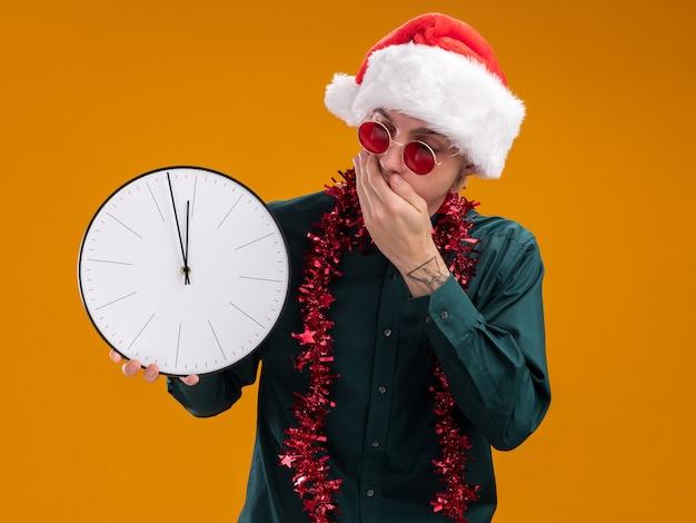 오렌지 배경에 고립 된 입에 손을 유지하는 시계를 들고 목 주위에 반짝이 갈 랜드와 산타 모자와 안경을 착용 우려 젊은 금발의 남자