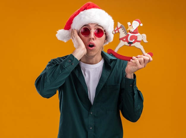 Concerned young blonde man wearing santa hat and glasses holding santa on rocking horse figurine looking at camera keeping hand on face isolated on orange background