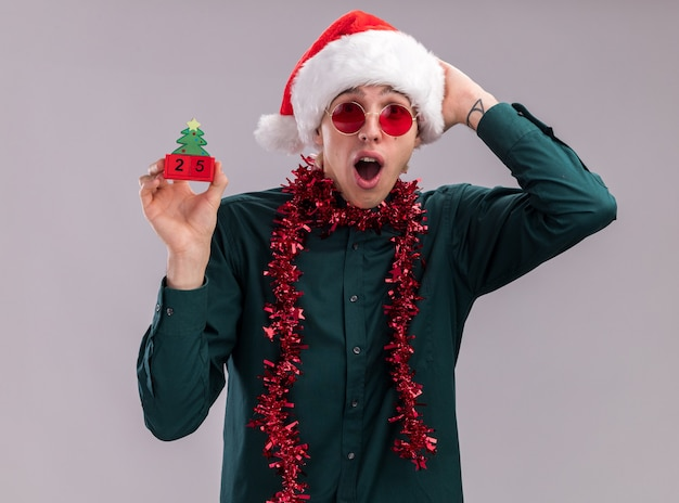 Concerned young blonde man wearing santa hat and glasses with tinsel garland around neck holding christmas tree toy with date looking at camera keeping hand on head isolated on white background