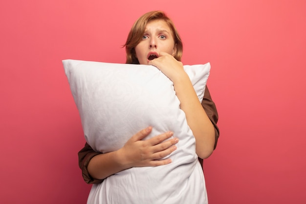 복사 공간이 있는 분홍색 벽에 격리된 정면을 바라보며 베개를 껴안고 걱정하는 젊은 금발 여성