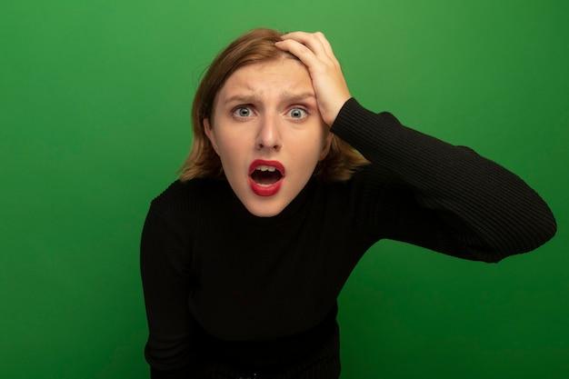 Preoccupato per la giovane donna bionda che mette la mano sulla testa guardando la parte anteriore isolata sul muro verde