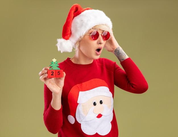 올리브 녹색 배경에 고립 된 측면을보고 날짜를 만지고 머리를 만지고 크리스마스 트리 장난감을 들고 안경 크리스마스 모자와 산타 클로스 크리스마스 스웨터를 입고 우려 젊은 금발의 여자
