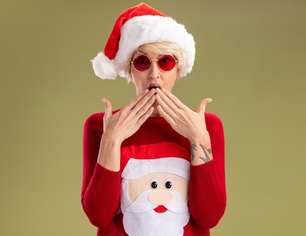Concerned young blonde woman wearing christmas hat and santa claus christmas sweater with glasses looking at camera keeping hands on mouth isolated on olive green background