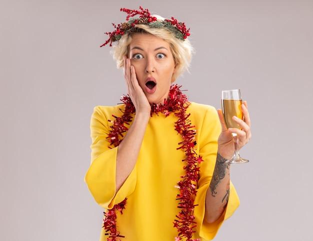 복사 공간이 흰 벽에 고립 된 얼굴에 유지 손을 찾고 샴페인 잔을 들고 목 주위에 크리스마스 머리 화환과 반짝이 갈 랜드를 입고 우려 젊은 금발의 여자