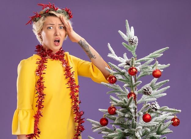 Обеспокоенная молодая блондинка в рождественском венке и гирлянде из мишуры на шее стоит возле украшенной елки, глядя в камеру, держа руку на голове, изолированную на фиолетовом фоне