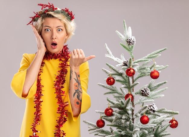 クリスマス ヘッド リースと見掛け倒しの花輪を身に着けている若いブロンドの女性が飾られたクリスマス ツリーの近くに立って、白い壁に孤立した側を指している顔の近くに手を保つ
