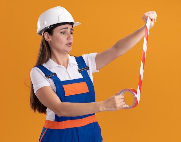 Preoccupato per la giovane donna del costruttore in uniforme che tiene il nastro adesivo allungato isolato sulla parete arancione