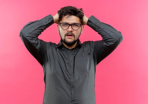 Обеспокоенный молодой бизнесмен в очках схватился за голову