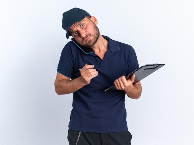 Preoccupato giovane fattorino caucasico in uniforme blu e cappuccio che tiene penna e appunti parlando al telefono