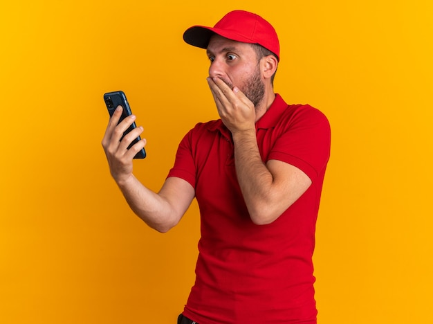 Concerned young caucasian delivery man in red uniform and cap holding and looking at mobile phone keeping hand on mouth isolated on orange wall