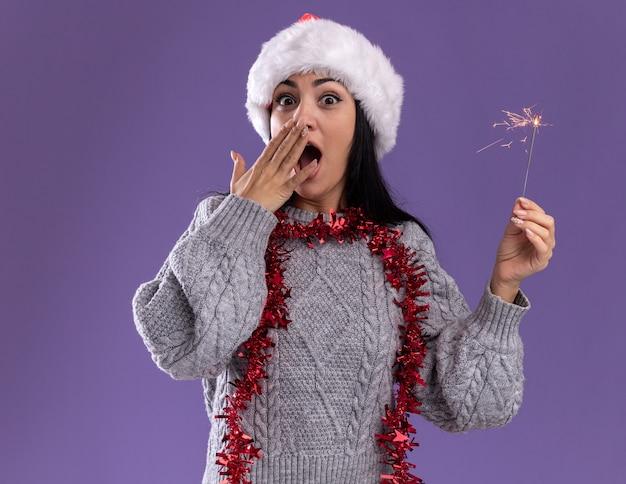 クリスマスの帽子と首の周りに見掛け倒しの花輪を身に着けている心配している若い白人の女の子は、紫色の背景で隔離の口に手を保ちながらカメラを見て休日の線香花火を保持しています