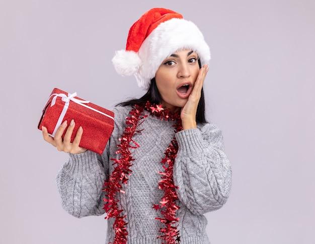 Preoccupato per la giovane ragazza caucasica indossando il cappello di natale e la ghirlanda di orpelli intorno al collo guardando la fotocamera tenendo il pacchetto regalo tenendo la mano sul viso isolato su sfondo bianco