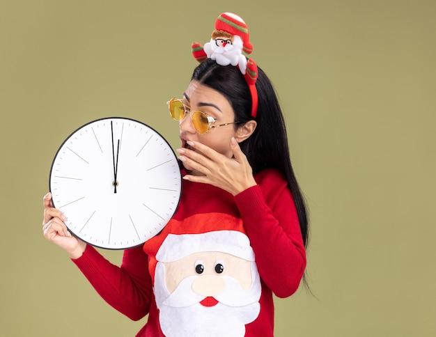 Обеспокоенная молодая кавказская девушка в головной повязке санта-клауса и свитере в очках держит и смотрит на часы, держа руку возле рта, изолированную на оливково-зеленой стене с копией пространства