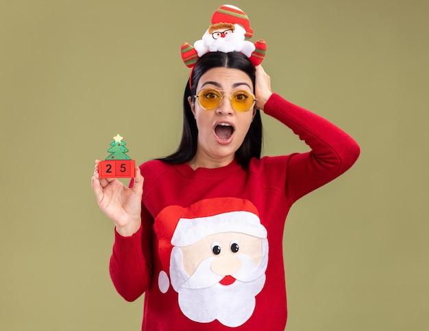サンタクロースのヘッドバンドとセーターを身に着けている心配している若い白人の女の子は、オリーブグリーンの背景に分離されたカメラを見て頭に手を置いてクリスマスツリーのおもちゃを保持している眼鏡をかけています