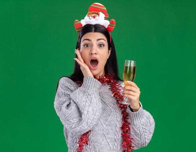 サンタクロースのカチューシャと見掛け倒しの花輪を首に巻いてシャンパンのグラスを持ち、緑の壁にコピースペースで隔離された顔に手をつないでいる、心配している若い白人の女の子
