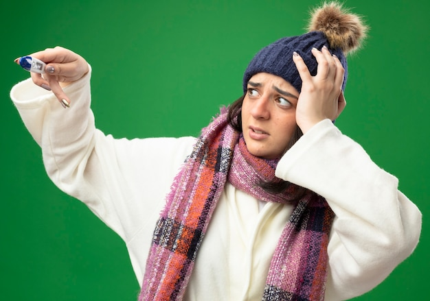 Giovane ragazza malata caucasica interessata che indossa cappello invernale e sciarpa della veste che tiene e che esamina il termometro che tiene la mano sulla testa isolata sulla parete verde