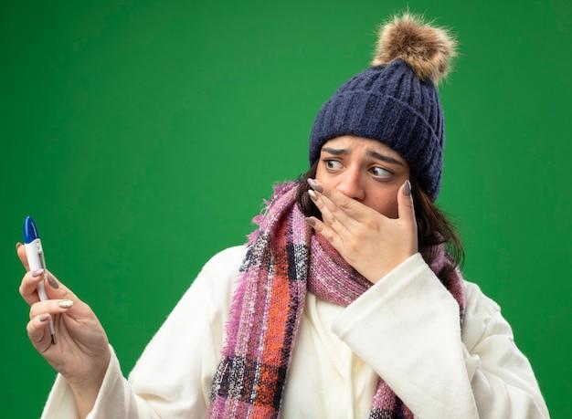 Giovane ragazza malata caucasica interessata che indossa il cappello e la sciarpa di inverno della veste che tengono e che esaminano il termometro che tiene la mano sulla bocca isolata sulla parete verde