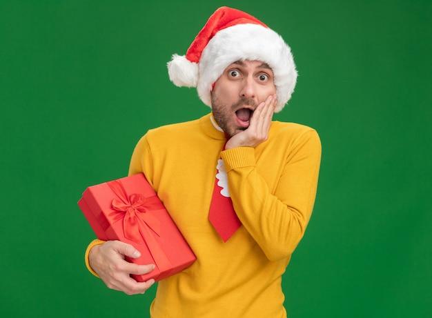 Обеспокоенный молодой кавказский мужчина в рождественской шляпе и галстуке держит подарочный пакет, держа руку на лице, глядя в камеру, изолированную на зеленом фоне