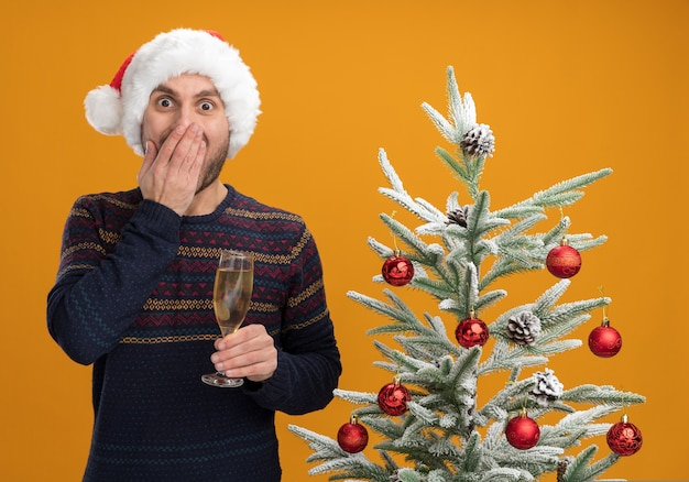 오렌지 배경에 고립 된 카메라를보고 입에 손을 유지 샴페인 잔을 들고 장식 된 크리스마스 트리 근처 서 크리스마스 모자를 쓰고 우려 젊은 백인 남자