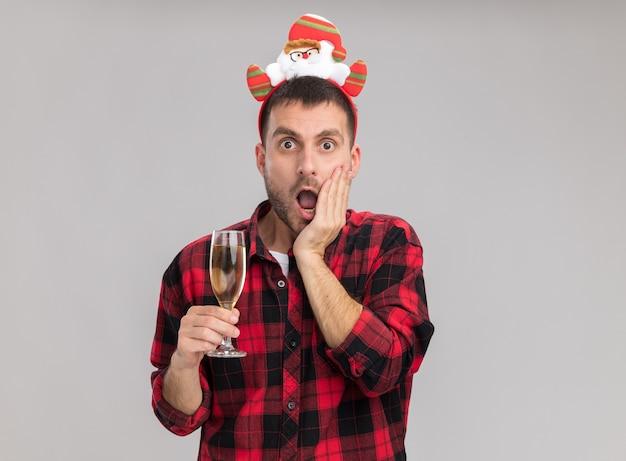 Giovane uomo caucasico interessato che porta la fascia di natale che tiene il vetro di champagne che guarda l'obbiettivo che tiene la mano sulla faccia isolata su fondo bianco