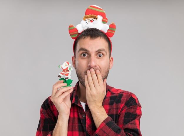 Giovane uomo caucasico interessato che porta il giocattolo di natale del pupazzo di neve della tenuta della fascia del babbo natale che guarda l'obbiettivo che tiene la mano sulla bocca isolata su fondo bianco