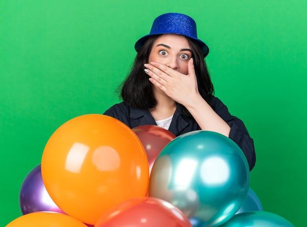 緑の壁に隔離された正面を見て口に手を保ち、風船の後ろに立っているパーティーハットを身に着けている心配している若い白人のパーティーの女性