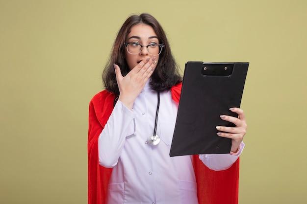 医者の制服と聴診器を身に着けている赤いマントで心配している若い白人のスーパーヒーローの女の子