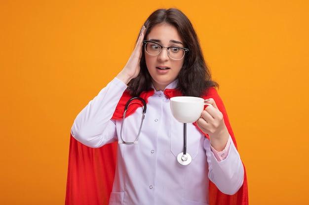 医者の制服と聴診器を身に着けている心配している若い白人のスーパーヒーローの女の子は、頭に手を置いてお茶を持って見ています