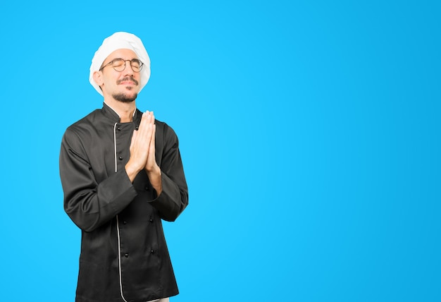 Concerned young chef praying gesture