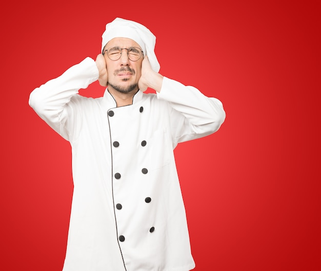 Concerned young chef worried about loud noises and covering his ears