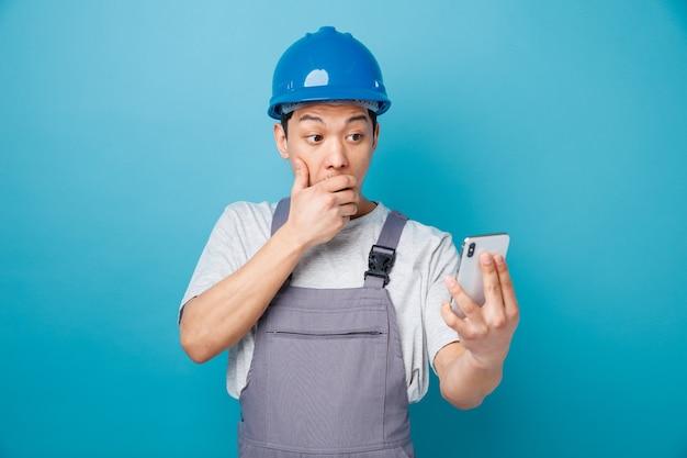 Preoccupato giovane operaio edile che indossa il casco di sicurezza e tenuta uniforme e guardando il telefono cellulare tenendo la mano sulla bocca