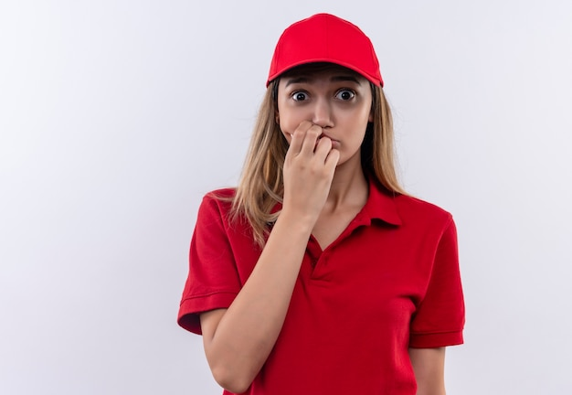 Обеспокоенная молодая доставщица в красной форме и кепке, положив руку на рот, изолированную на белой стене