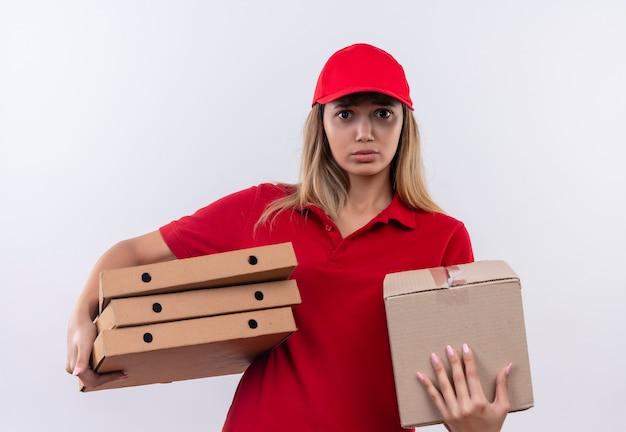 Ragazza di consegna giovane interessata che porta l'uniforme rossa e la scatola della tenuta del cappuccio e le scatole per pizza isolate sulla parete bianca