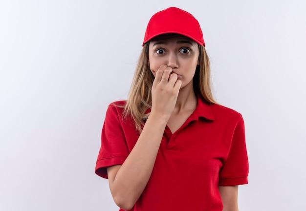 La giovane ragazza di consegna interessata indossa l'uniforme rossa e il cappuccio che mette la mano sulla bocca isolata sul muro bianco
