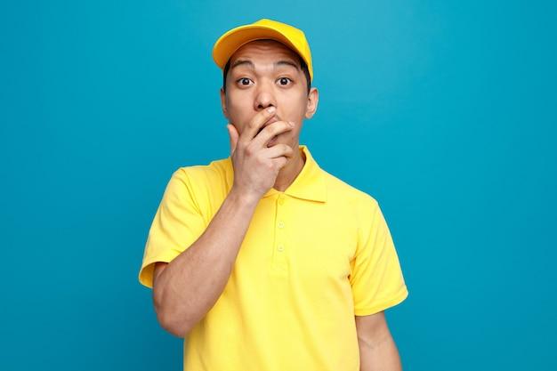 Giovane uomo di consegna interessato che indossa l'uniforme e il cappuccio che fa il gesto oops