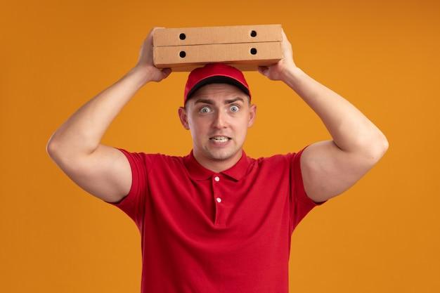오렌지 벽에 고립 된 머리에 피자 상자를 들고 모자와 유니폼을 입고 우려 젊은 배달 남자