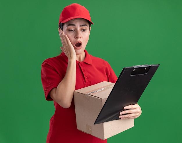 クリップボードを見てカードボックスとクリップボードを保持している制服とキャップで心配している若い配達の女性