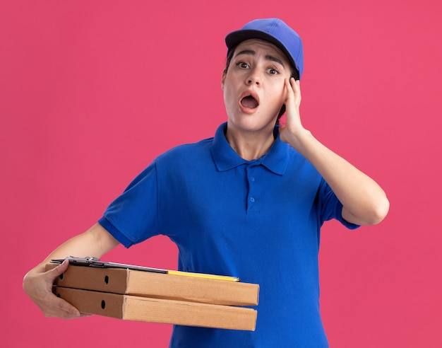 유니폼을 입고 모자를 쓴 젊은 배달 여성이 얼굴에 클립보드가 달린 피자 패키지를 들고 있다
